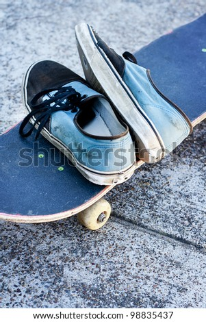 pair of worn out sneakers against concrete background - stock photo