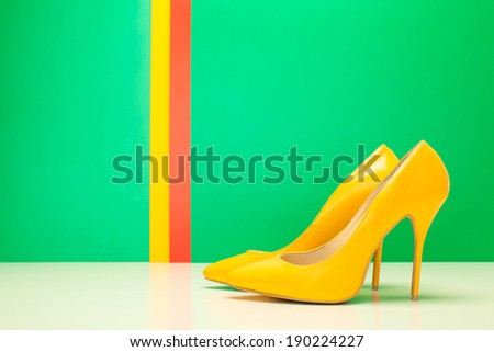 pair of yellow high heels on green and stripes background - stock photo