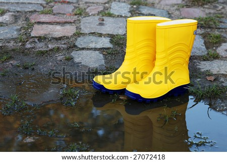 Pair of yellow rubber boots beside a puddle - stock photo