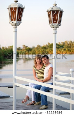 Pair on a pier. Look at cam. - stock photo