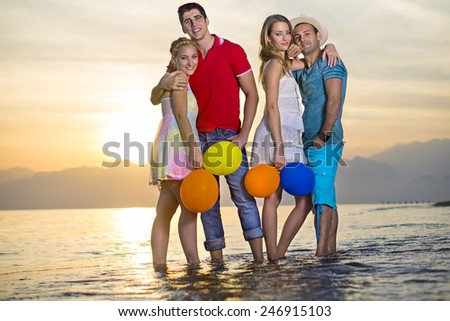 Pairs of Sweet Young Couples Posing at the Sea Water During Sunset Time. - stock photo