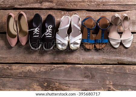 Pairs of woman's stylish footwear. Shoes on old wooden shelf. Shoe row at vintage store. Retro boutique footwear sale. - stock photo