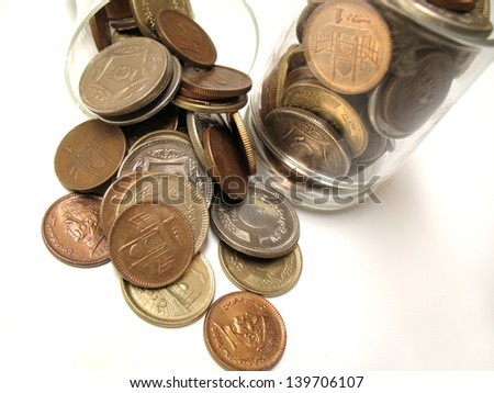 Pakistani coins in jar and on the floor - stock photo