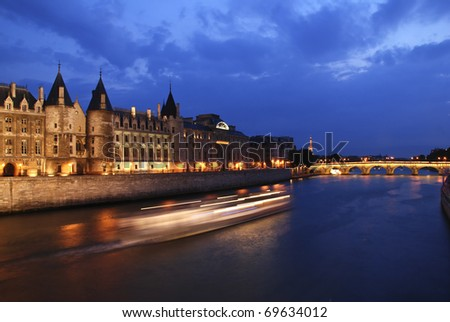 Palais de Justice standing on the banks of river Seine on the island Il de la Cite, Paris - France after the sunset with a boat passing by - stock photo