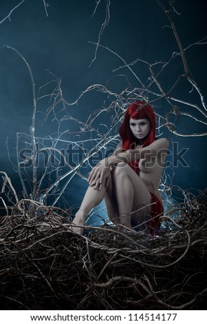 Pale redhead nude woman in forest, Halloween theme - stock photo