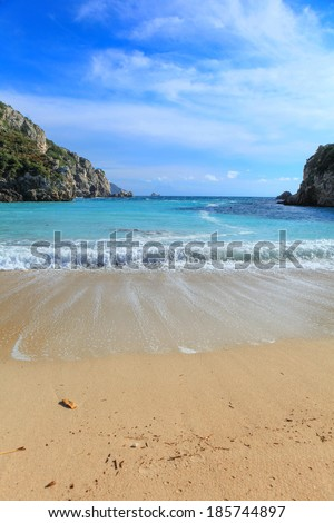 Paleokastritsa beach on Corfu, Greece, looking out between the two headlands, vertical composition - stock photo