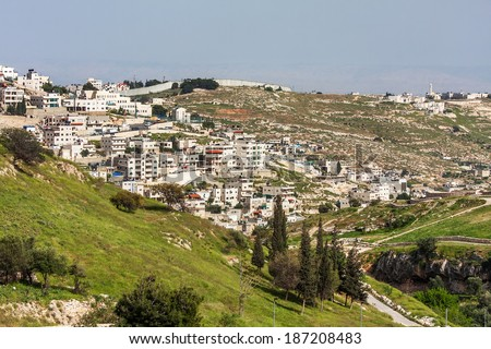 Palestinian town on suburb of Jerusalem and West Bank israeli separation barrier on background. - stock photo