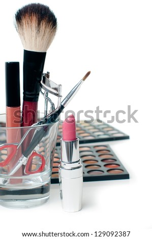 Palette of colorful eyeshadows, lipstick, eyelash curlers and  make-up brushes, close-up, isolated - stock photo