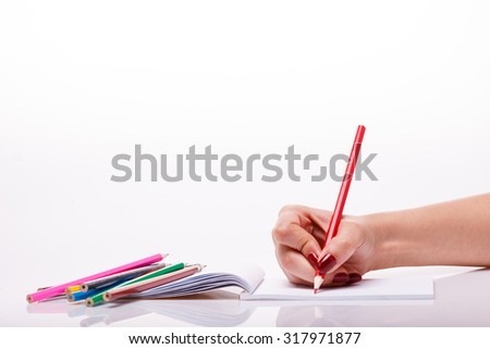Palette set of colorful pencils brown red yellow blue green violet pink purple lilac and orange colors lying near drawing human hand on paper sheet on white background copyspace, horizontal picture - stock photo