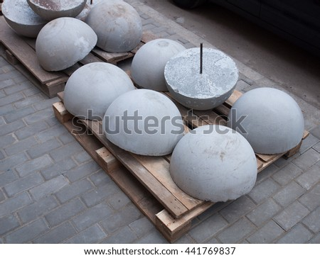 Pallet of concrete grey spheres to restrict the movement cars on the sidewalk - stock photo