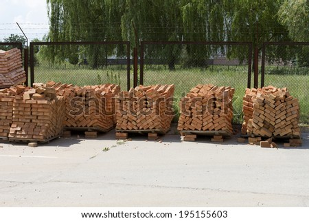 Pallets with red bricks on a construction site. - stock photo