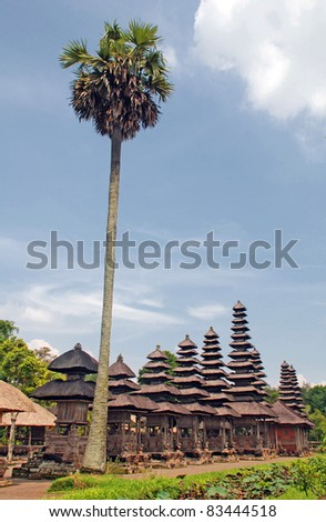 Palm and Taman Ayun Temple in Mengwi (Bali, Indonesia) on a beautiful sunny day. Originally dated from 1634. - stock photo