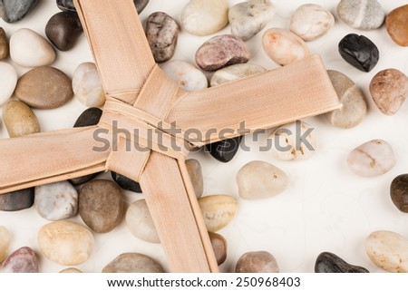 Palm Cross set on multi colored stones. Background for Easter, Good Friday or Palm Sunday. - stock photo