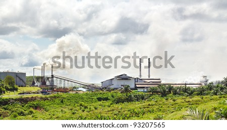 Palm Oil crushing industrial site in operation in a newly planted palm oil plantation Malaysia - stock photo