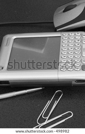 Palm Pilot, paper clips, stylus, mouse - stock photo