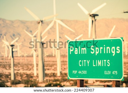 Palm Springs City Limits Highway Sign and Wind Turbines in the Background. Palm Springs, California, USA. - stock photo