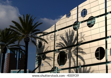 Palm tree shadows are cast upon a wave-shaped parking garage in Long Beach, California. - stock photo