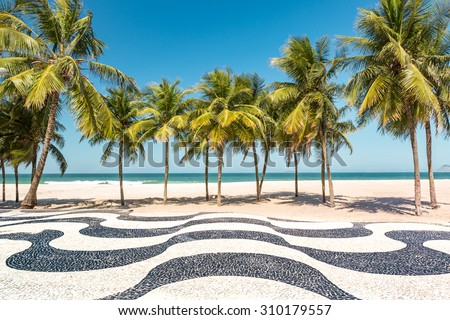 Palm trees and the iconic Copacabana beach mosaic sidewalk, in Rio de Janeiro, Brazil. - stock photo