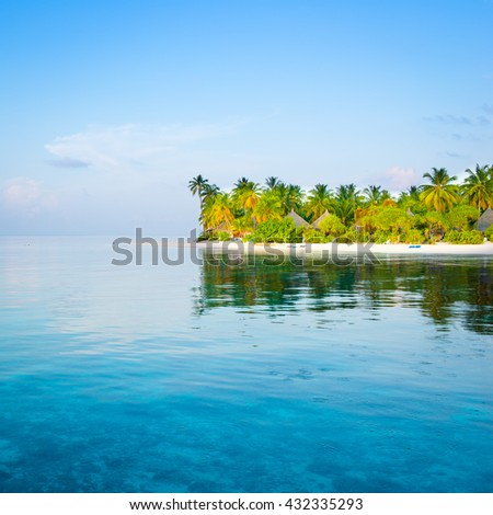 Palm trees on a tropical island in the Indian Ocean. Turquoise water in the lagoon. - stock photo