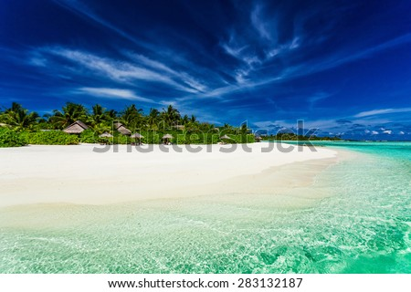 Palm trees over stunning lagoon and white sandy beach in Maldives - stock photo