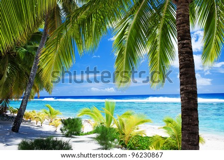 Palm trees overlooking amazing blue lagoon and white beach - stock photo