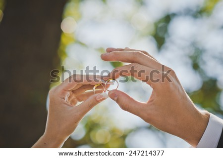 Palms of the newly-married couple with wedding rings in fingers. - stock photo