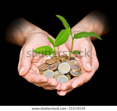 Palms with plants growing from pile of coins - stock photo