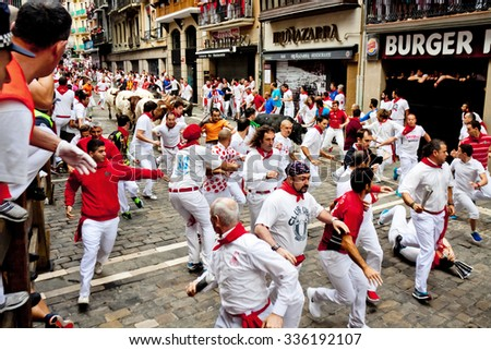 PAMPLONA, SPAIN - JULY 8, 2015: Bulls and people are running in street during San Fermin festival. Festival has been held annually for several centuries - stock photo