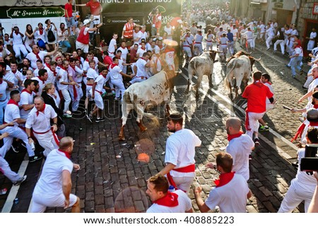 PAMPLONA, SPAIN - JULY 7, 2015: Bulls and people are running in street during San Fermin festival. Festival has been held annually for several centuries - stock photo