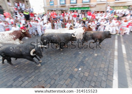 PAMPLONA, SPAIN - JULY 12: People run from bulls on street during San Fermin festival in Pamplona, Spain on July 12, 2015 - stock photo