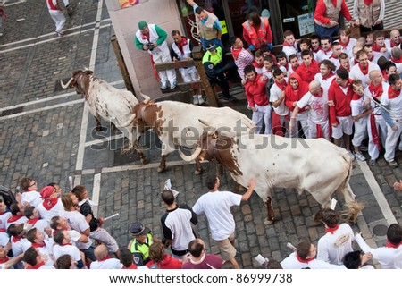 PAMPLONA, SPAIN -JULY 8: Unidentified men run from the bulls in the street Estafeta during the San Fermin festival in Pamplona, Spain on July 8, 2011. - stock photo