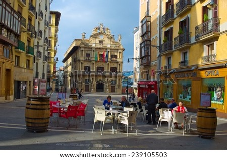 PAMPLONA, SPAIN, OCTOBER 25, 2014: People are having lunch in a restaurant in front of the town hall in spanish city pamplona. - stock photo