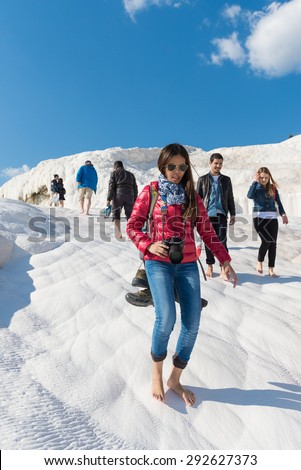 PAMUKKALE, TURKEY- APRIL,12: Tourists on Pamukkale travertines on April 12, 2015 in Pamukkale, Turkey. Pamukkale, UNESCO world heritage site, nowadays become one of the most visited sights in Turkey.  - stock photo