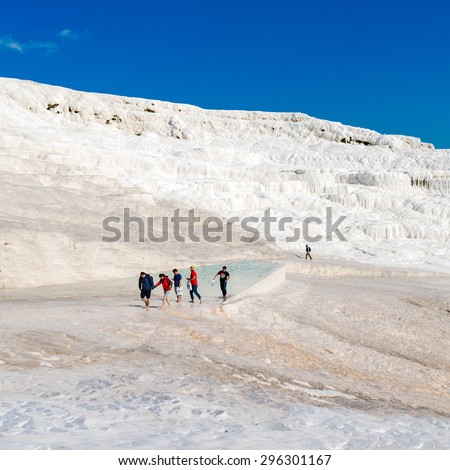PAMUKKALE, TURKEY- APRIL,12: Tourists on Pamukkale travertines on April 12, 2015 in Pamukkale, Turkey. Pamukkale, UNESCO world heritage site, nowadays become one of the most visited sights in Turkey - stock photo