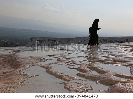 """PAMUKKALE, TURKEY - AUGUST 11, 2015: A Muslim woman walking on the terraces at Pamukkale.  It """"cotton castle"""" in Turkish and is natural site in southwest Turkey, that attracts many tourists.  - stock photo"""