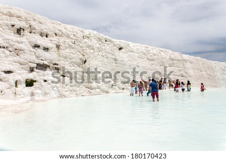 PAMUKKALE, TURKEY - MAY, 31: Tourists on Pamukkale travertines on May 31, 2013 in Pamukkale, Turkey. Pamukkale, UNESCO world heritage site, nowadays become one of the most visited sight in Turkey - stock photo