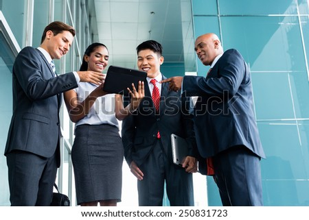 Pan Asian and Caucasian business team looking at tablet computer watching presentation of new project - stock photo