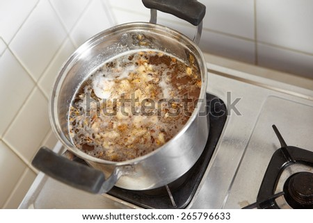 Pan filled with water and all ingredient for chicken porridge - stock photo