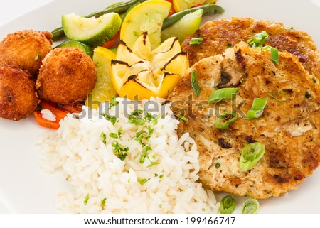 Pan fried crab cake sandwich served with a side of rice, vegetable medley and hush puppies. - stock photo