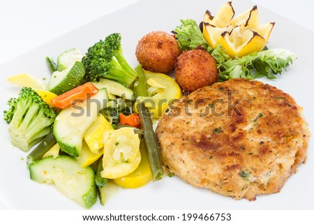 Pan fried crab cake sandwich served with a side of vegetable medley and hush puppies. - stock photo