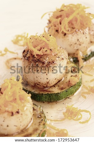 Pan fried scallops with citrus zest on plate, close-up, toned image - stock photo