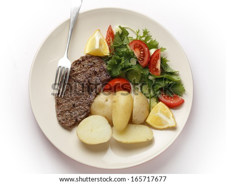 Pan-grilled pepper minute steak served with a salad of fresh leaves, tomato, cucumber and lemon with boiled new potatoes - stock photo