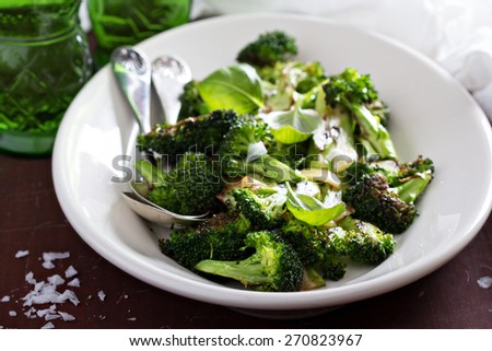 Pan roasted broccoli with crispy garlic on plate - stock photo