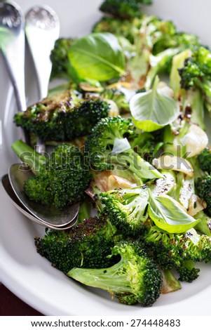 Pan roasted broccoli with crispy garlic on plate - stock photo