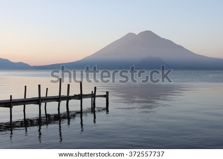 Panajachel, Guatemala - Lake Atitlán at sunrise, wooden pier and volcanoes in the background. - stock photo