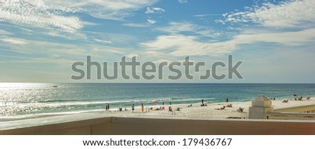 PANAMA CITY, FL - FEB. 22, 2014:  Beach goers enjoy beach and blue water of the Gulf of Mexico.  Panama City Beach is a very popular spring break destination  during the months of March and April. - stock photo