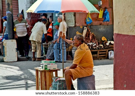 PANAMA CITY, PANAMA, DECEMBER 20 2006.  A man sitting under an umbrella, selling cigarettes, in the old part of Panama City, on December 20th 2006. FOR EDITORIAL USE ONLY - stock photo