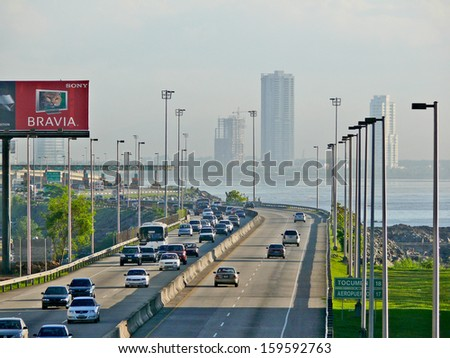 PANAMA CITY, PANAMA, DECEMBER 20 2006. Cars driving in the highway with a skyscraper, sea and cloudy sky in the background, in Panama City, on December 20th 2006.  - stock photo