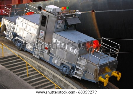 PANAMA - OCTOBER 6. In July 2009, the Panama Canal Authority awarded contracts to a consortium of companies to build six new locks by 2015. Ship towing locomotive at Balboa. October 6, 2010, Panama - stock photo