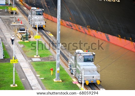 PANAMA - OCTOBER 6. In July 2009, the Panama Canal Authority awarded contracts to a consortium of companies to build six new locks by 2015. Locomotives towing a ship at Balboa. October 6 2010, Panama - stock photo